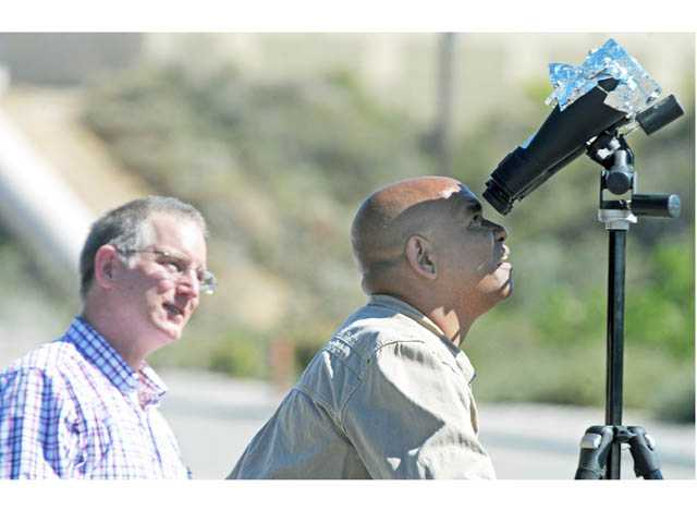 "Rick Bell, of Acton, right, looks at the Transit of Venus through binoculars fitted with mylar film set up by Tom Wells of Saugus, left, on the parking lot outside Babies ""R"" Us on Carl Boyer Drive in Santa Clarita on June 5."