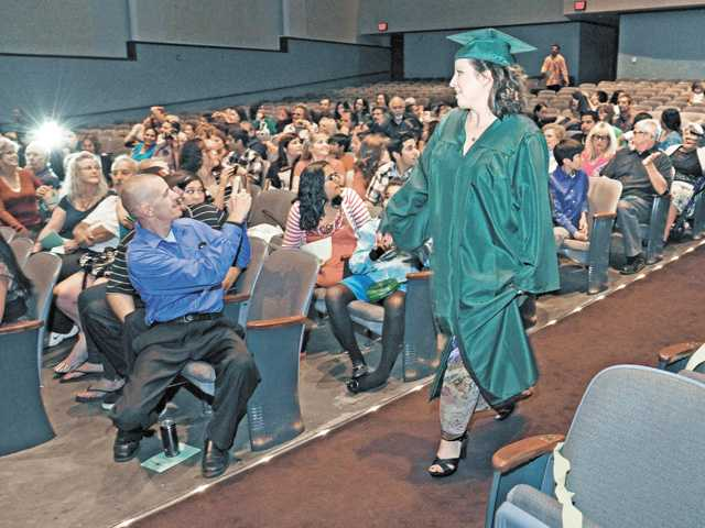 Family and friends photograph Golden Oak Adult School graduates as they enter the graduation ceremony for the 2012 adult school class held in the Hart High School auditorium in Newhall on June 5.