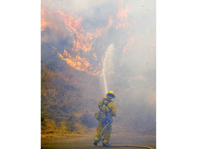 A Los Angeles County firefighter begins an attack on a fire burning down a hill off the northbound lanes of Interstate 5 north of Castaic on June 8.