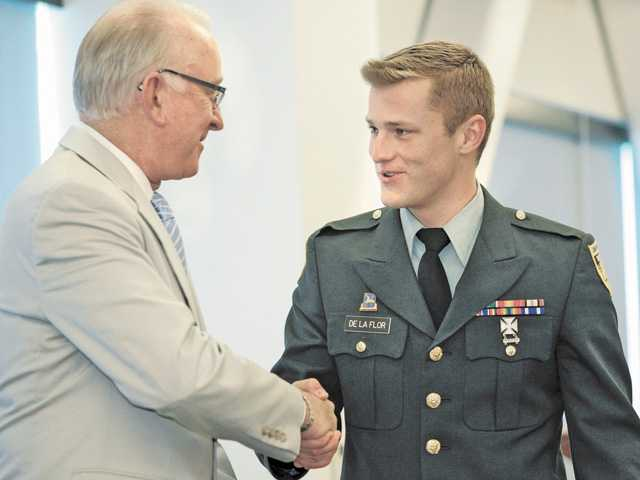 "Local Military Academy Appointee Nicholas De La Flor (cq), right, of Valencia, shakes hands with U.S. Representative Howard ""Buck"" McKeon after being recognized at the 2012 Service Award Luncheon held at the Dr. Dianne G. Van Hook University Center in Valencia on June 9."