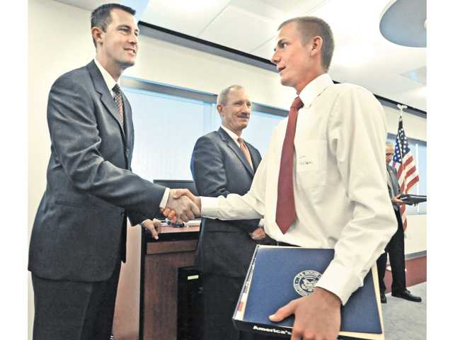 Local Military Academy Appointee Sam Peckham, right, of Valencia, shakes hands with military guest Greg Waugh representing the United States Military Academy after Peckham was recognized at the 2012 Service Award Luncheon held at the Dr. Dianne G. Van Hook University Center in Valencia on June 9.