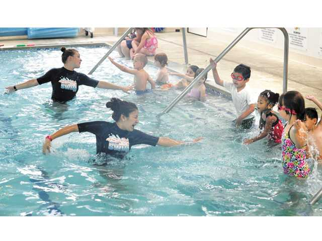 Swim instructors Bailey Campbell, top, and Selene Cervantes demonstrate an alternating arm stroke.