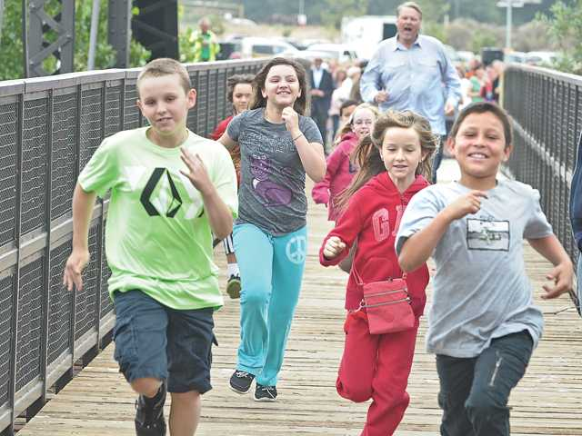 Santa Clarita Mayor Frank Ferry, rear, races Santa Clarita children across the bridge at the Iron Horse Trailhead grand opening ceremony in Valencia on Friday.