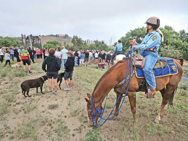 Sue Winthers of County of Los Angeles Parks and Recreation Mounted Assistance Unit applauds the speeches as she and her mount Bob attend the Iron Horse Trailhead grand opening ceremony in Valencia on Friday.