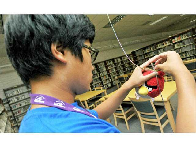 "Ivan Kim, 15, hangs a stuffed Angry Bird from the ceiling as volunteers set up a scene for the ""Stuffed Animal Sleep-Over"" at the Valencia Library on Friday."