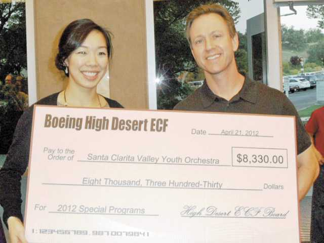 Emily Wong and Thomas Armfield of Boeing Company with the Boeing Company's grant check of $8,330.