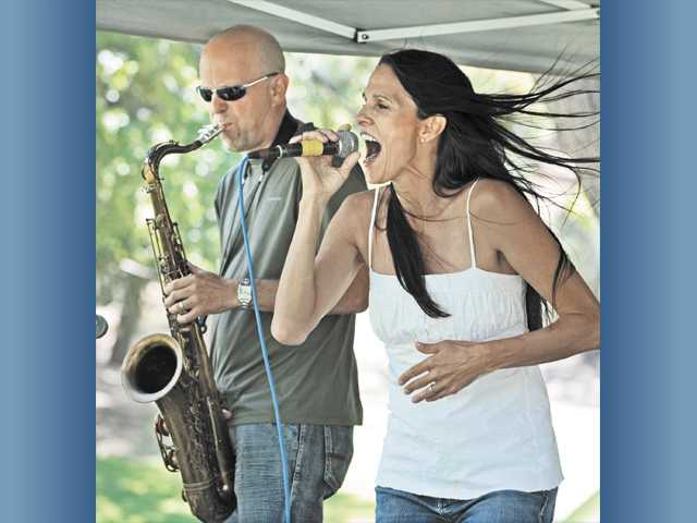 Bill Johnston, left, on sax, and lead singer Kelly Zirbes of Kelly's Lot perform with their band.