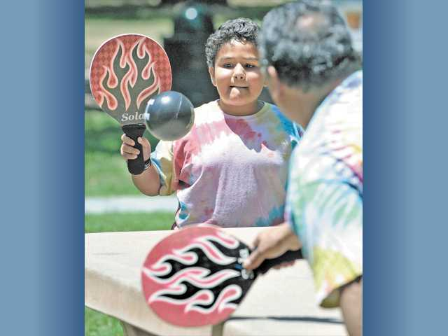 Julian Duarte, 8, of Newhall, plays paddle ball with grandfather Robert Duarte as they listen to the music.