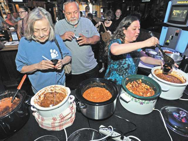 From left, Gillian Lange, Nick Peterson and Kim Valis sample from six crockpots of chili in the Broken Trail Chili Cook-Off contest and fundraiser held at The Vu Bar & Lounge in Newhall on Saturday. See A8 for more pictures.