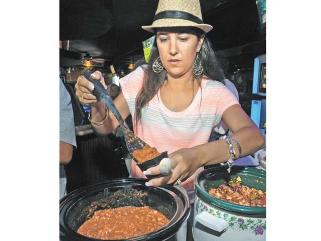 Jenny Ketchepaw samples one of the six crock-pots of chili.