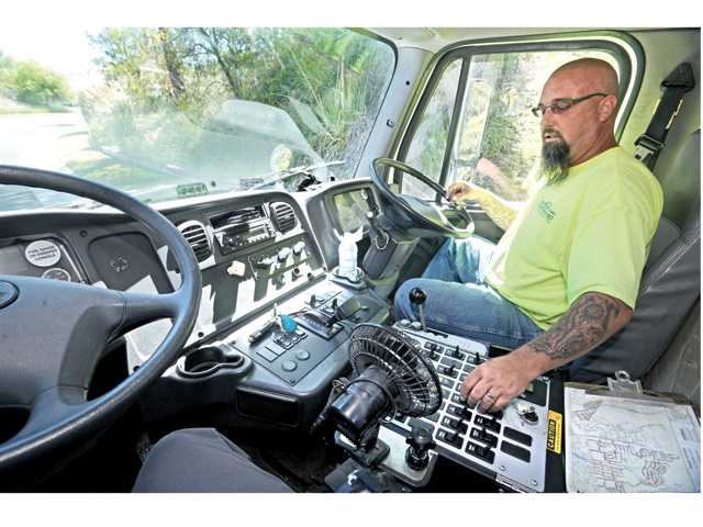 Clean Sweep Environmental driver Jonathan Harding adjusts the controls of the street sweeper in an area in Sand Canyon on Friday.