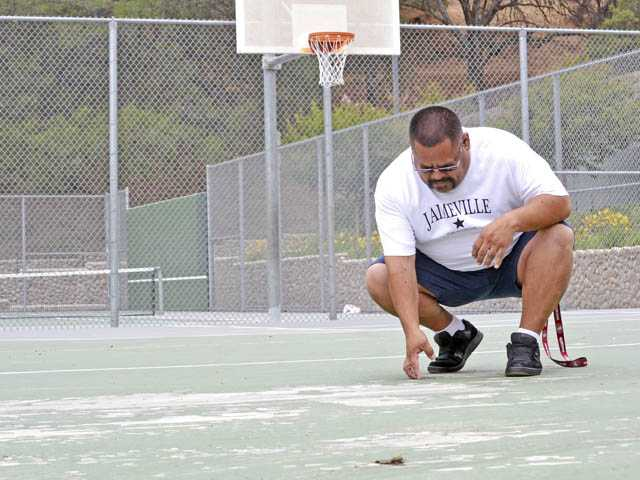 Youth Activity League official Jaime Briano looks at chips in the surface of the Val Verde Park basketball court on Friday.