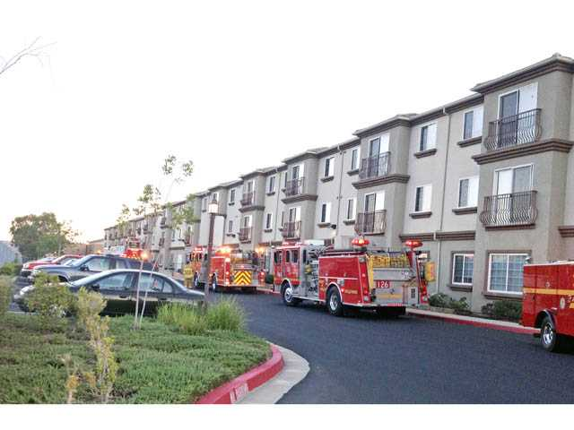 Firefighters are stationed at the scene of a fire in a third-floor unit at the Castaic Lake Senior Village on Sunday evening.