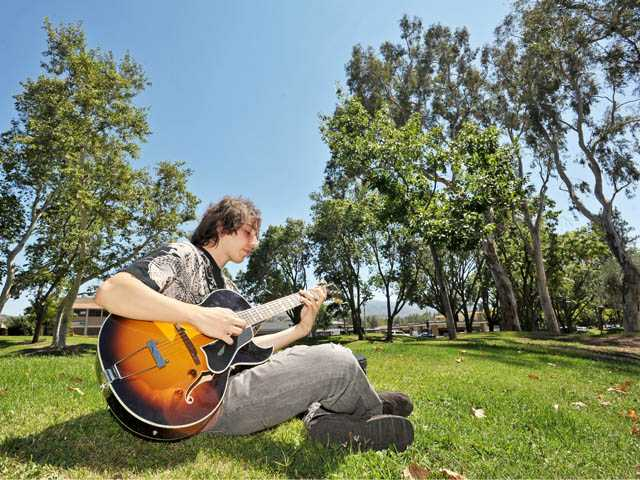 Andrea Balestra practices his guitar at Old Orchard Park in Newhall on Monday.