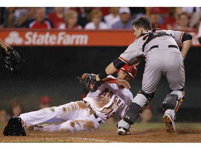 Los Angeles Angel Maicer Izturis, left, is tagged out out by San Francisco Giants catcher Buster Posey while trying to score on a ball hit by Mike Trout in Anaheim Monday.