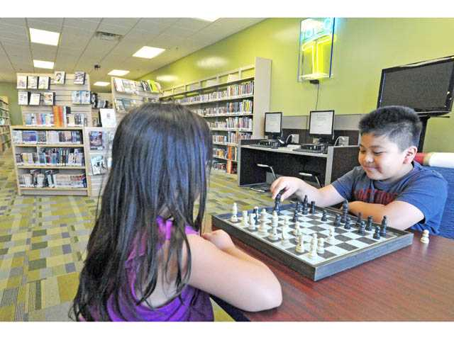 Siblings Hannah, 7, left, and Joshua Vitor, 10, play chess in the teen area of the Castaic Public Library on Tuesday.