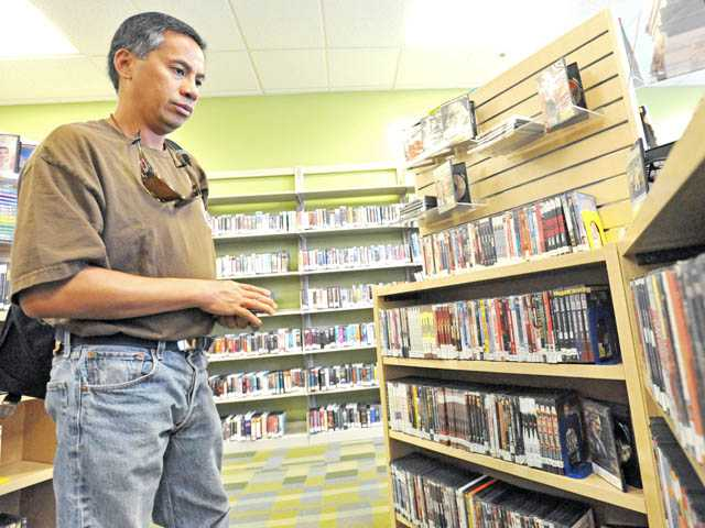 Bill Velasco, of Castaic, browses through DVDs at the Castaic Public Library on Tuesday.