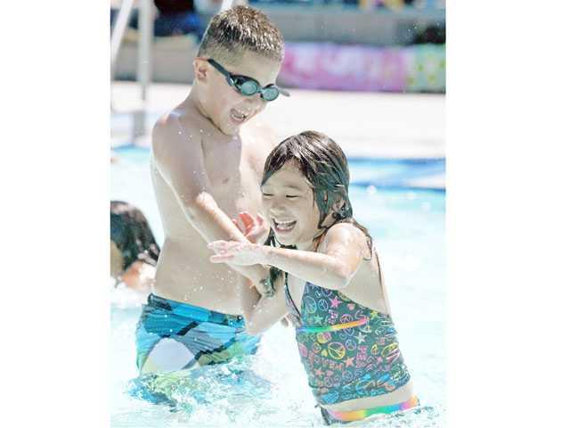Felix Garcia, 9, left, and Asha Joo, 7, play in the activity pool at the Santa Clarita Aquatic Center on Tuesday. 061912