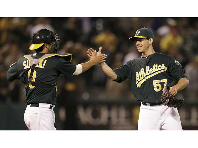 Oakland Athletics pitcher and Saugus High graduate Tommy Milone, right, is congratulated by catcher Kurt Suzuki after beating the Los Angeles Dodgers on Wednesday in Oakland. Milone threw his first career complete game.
