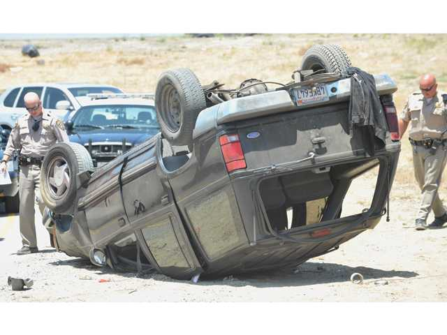 California Highway Patrol officers gather evidence at the scene where a Ford SUV rolled off the Newhall Avenue off-ramp of northbound Highway 14 on Wednesday afternoon.