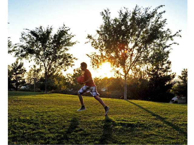 Daniel Osorio, 14, heads to the basketball courts as the sun sets over Pamplico Park in Saugus to mark the end of the first day of summer on Wednesday.