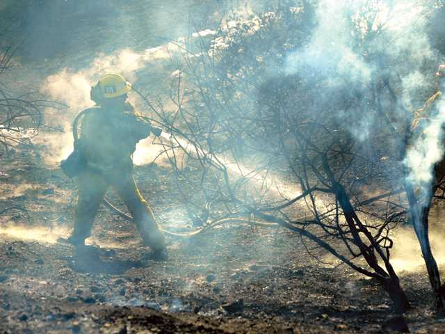 A firefighter from Fire Station 111 sprays water on a two-acre fire that burned up a steep slope under power lines Seco Canyon Road and Fig Court in Saugus.