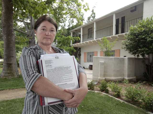 DeAun Tollefson holds the notice of trustee sale, outside her home in Sacramento on Friday.
