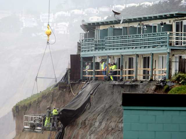In this Jan. 26, 2010, photo, workers conduct repairs on an apartment complex on a crumbling cliff after a series of storms in Pacifica.