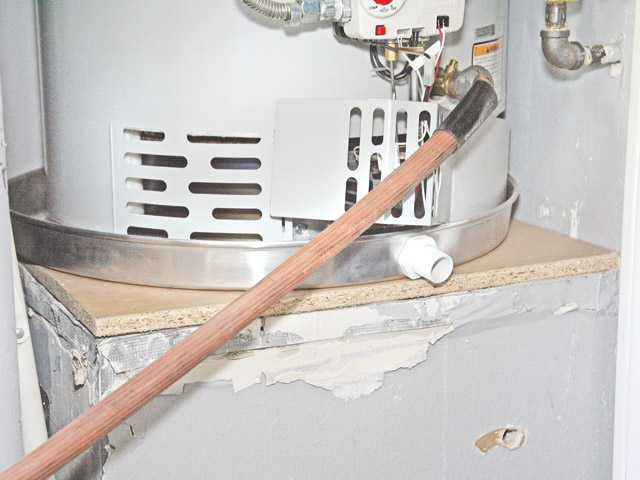 The hose is stretched through the garage to the outside where the water from the water heater drains into a strainer.
