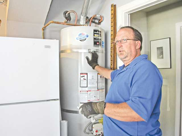 Plumber Kirk Stinson of Plumbing by Kirk prepares to drain a water heater installed 18 months ago in the Saugus home of David Herzer and Lynn Holmgren.
