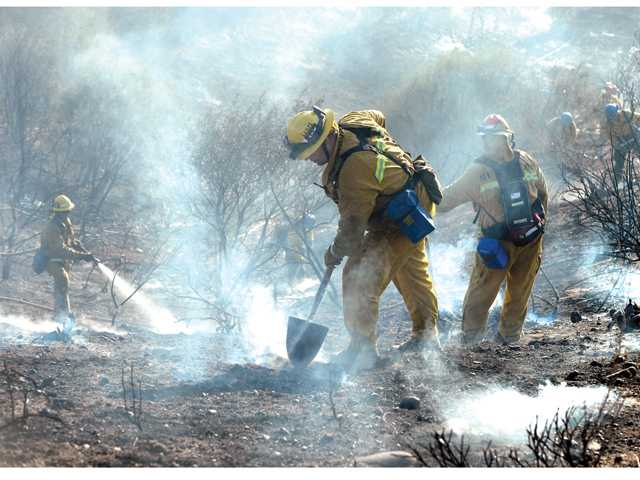 Firefighters use hand tools and fire hoses to fight a two-acre fire that burned up a steep slope under power lines near Seco Canyon Road in Saugus on Thursday.