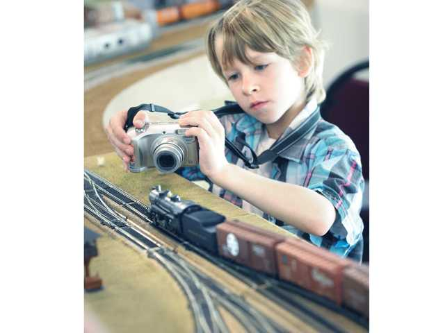 James Violet, 8, of Santa Clarita takes a photo of a passing engine.