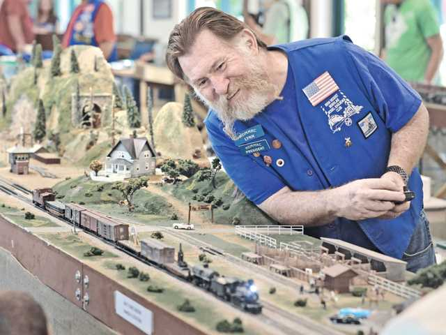 High Desert Modular Model Railroad Club president Lynn McCurdy uses a wireless remote to control a model train as it runs on a 70-foot-long modular HO-scale railroad layout presented by High Desert Modular Model Railroad Club at William S. Hart Park's Hart Hall in Newhall on Saturday.