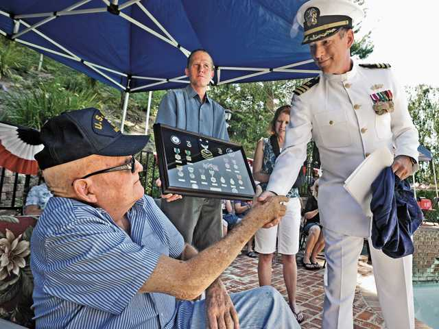 Master Chief Stuart Bird, a 30-year veteran of the U.S. Navy Seabees, left,  shakes hands with U.S. Navy Cmdr. Thomas Sutton. Bird's son Shannon Bird, center, and daughter Shauna Bird present him with his medals at a ceremony held at Bird's brother's home in Saugus on Saturday.