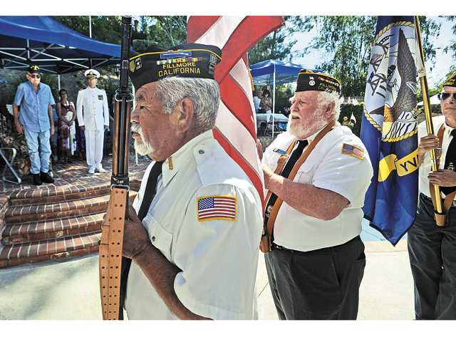 Stuart Bird and Sutton stand at attention as members of the Veterans of Foreign Wars Color Guard of Fillmore present the colors.