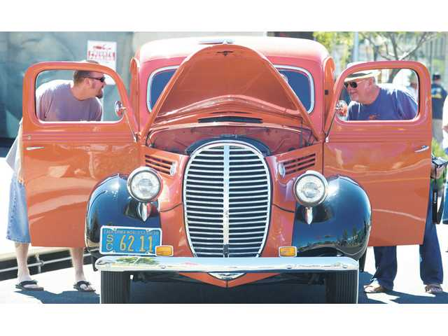 Car exhibitors Colin McCormick, left, and father, Mike, of Valencia, look at the interior of  a 1939 Ford flathead, one of  dozens of pre-1957 cars on display at the third annual Old Town Newhall Car Show held on Main Street in Newhall on Sunday.