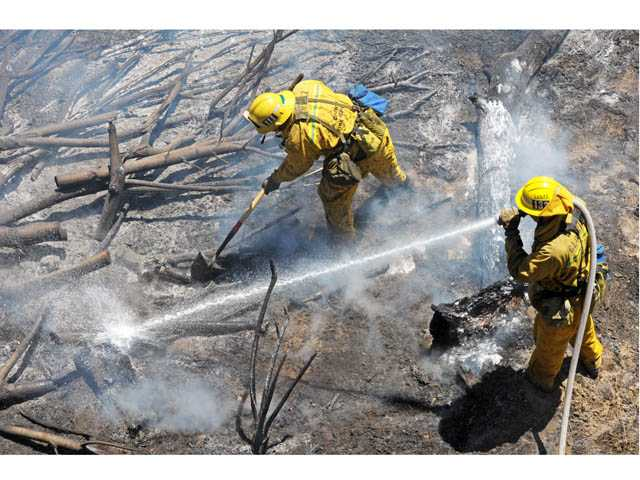 Firefighters mop up after a fire charred brush in the San Francisquito Creek bed in Valencia on Tuesday.