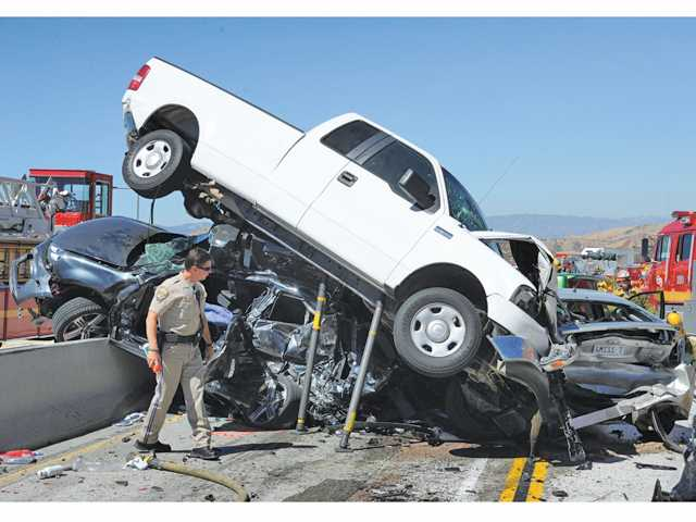 Three vehicles are stacked on the center divider at the scene of a traffic collision on the southbound 14 freeway south of Escondido Canyon Road near Acton involving and many injuries as CHP and firefighters work to clear the crash on Tuesday morning.