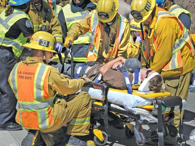 The occupant of one of 19 vehicles involved in at traffic collision on the southbound 14 freeway south of Escondido Canyon Road near Acton is prepared for transportation in waiting ambulances as CHP and firefighters work to clear the crash on Tuesday morning.