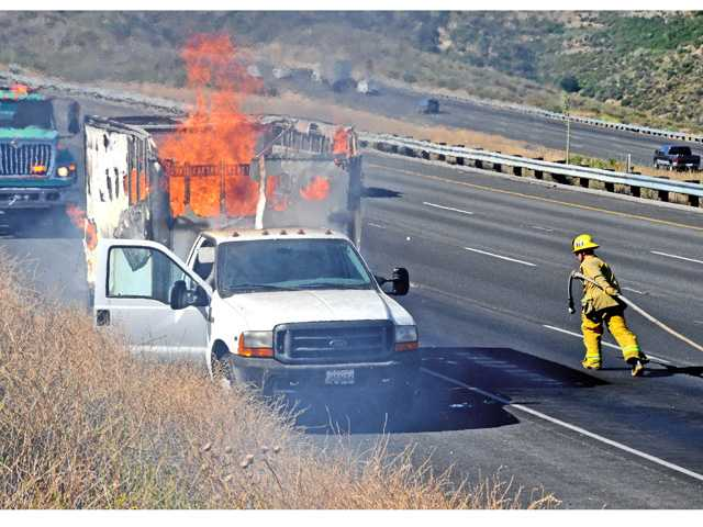 Los Angeles County firefighters, assisted by crews from the U.S. Forest Service, work to control a fire that fully engulfed a truck on the northbound Interstate 5 north of Templin Highway on Wednesday morning.  The fire spread to the grass and brush along the freeway and consumed about three-quarters of an acre.