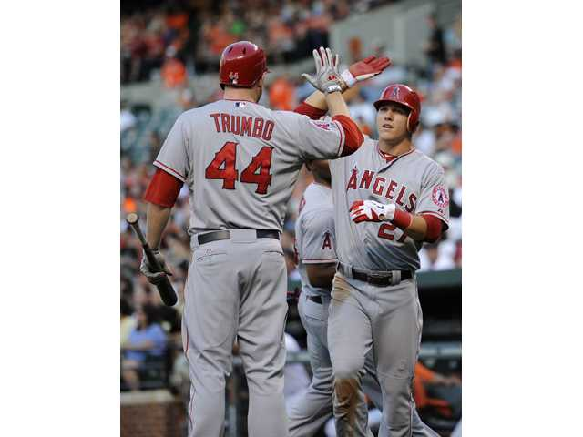 Los Angeles Angel Mike Trout (27) celebrates with Mark Trumbo (44) after he scored on a single by Kendrys Morales against the Baltimore Orioles on Wednesday in Baltimore.