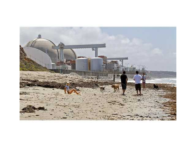 In this Friday, April 27, 2012, file photo, people utilize the beach outside the San Onofre Nuclear Generating Station in San Onofre.