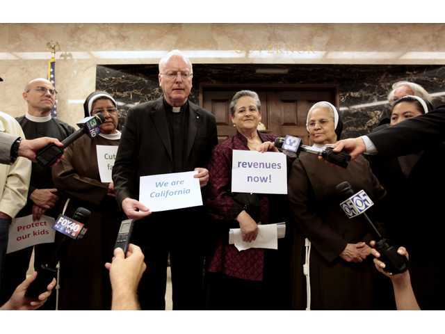 Father Michael Kiernan, from the Cathedral of the Blessed Sacrament, third from left, accompanied by nuns from the Franciscan Sisters of the Immaculate Conception of Los Angeles, and others, hold a prayer vigil to protest the state budget agreement