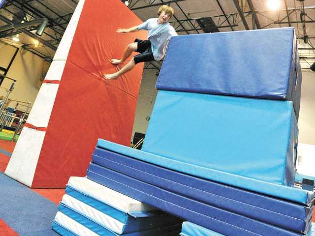Joey Dubiel, 16, launches a wall flip off the floor and onto padded obstacles during a parkour class at Hugo's Gymfitness in Santa Clarita on Tuesday night.
