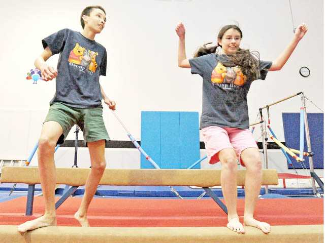 Siblings Christopher, left, and Christabel Eickemeyer practice precision jumps between beams during a class