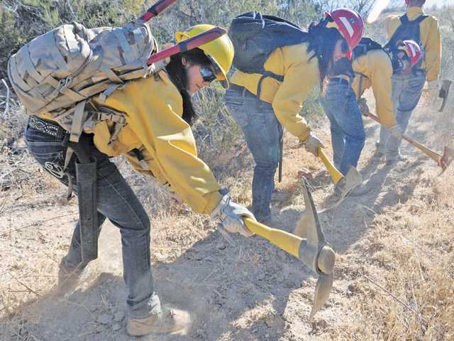 Team leader Stephanie Velazquez, 18, left, and other members of the Hart district's Trails program use axes to clear a path on Snake Trail in Quigley Canyon Open Space in Santa Clarita on Thursday.