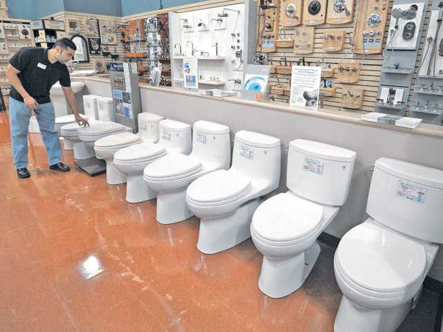 Armando Cruz, plumbing manager at Pacific Sales in Valencia, points out a wall-mounted toilet that is easy to clean under. Four one-piece toilets and two two-piece toilets are in the foreground. All feature 1.28 gallon flush.