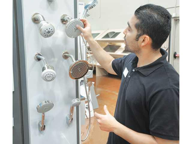 Cruz shows the rub-to-clean nozzle on a Hansgrohe shower head.