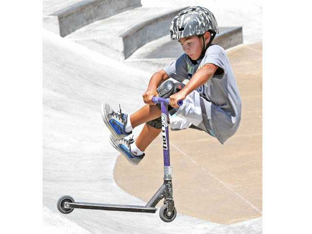 Luke Draper, 9, performs a tail whip on his scooter at the skate park.
