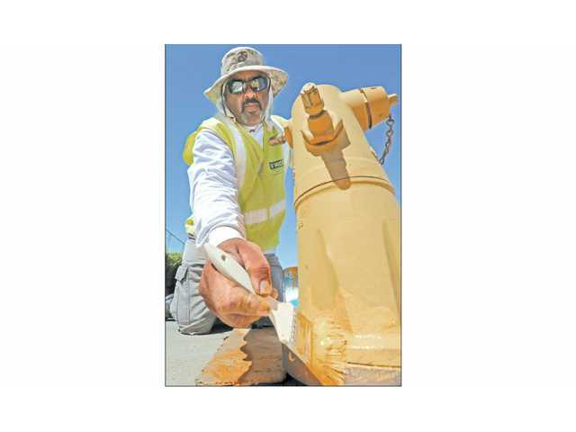 Ruben Taube, a foreman for Staats Construction under contract to Valencia Water Co.,  paints a fire hydrant on Valencia Boulevard in Valencia recently.